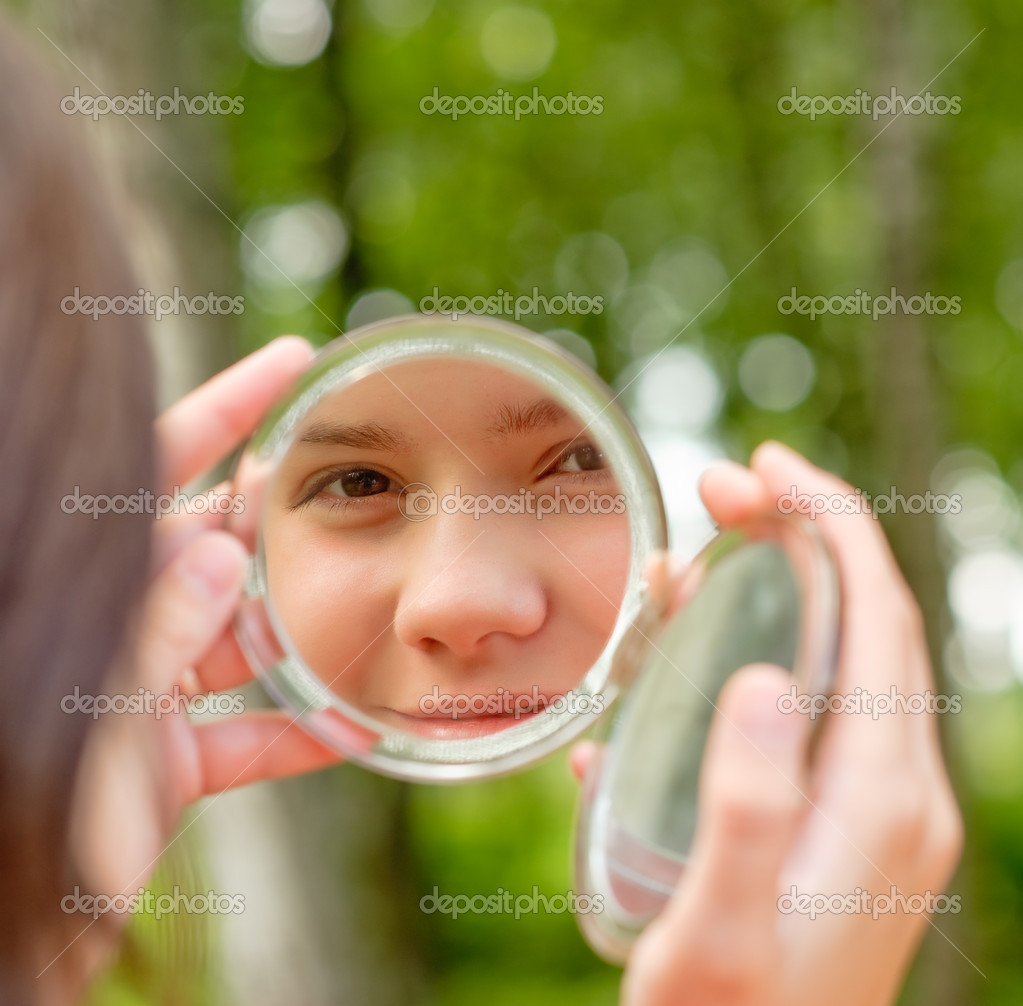 Lovely girl looks in round mirror against summer green park. — Stock Photo #1610591