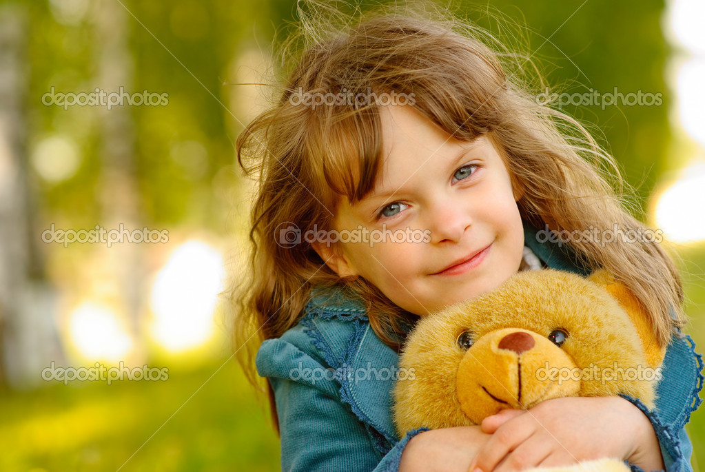 The small beautiful girl embraces an amusing bear cub against summer nature. — Stock Photo #1610667