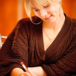 Stock Photo: Blonde writes to writing-books