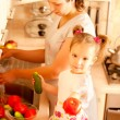 Mum with daughter on kitchen - Stock Photo
