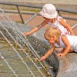 Sisters play at fountain — Stock Photo