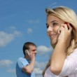 Girl and young man speak by phone — Stock Photo