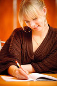 Blonde writes to writing-books — Stock Photo