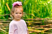 Little girl at wattled protection. — Stock Photo