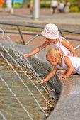 Sisters play at fountain — Stockfoto
