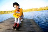 Ragazza si siede sul ponte — Foto Stock