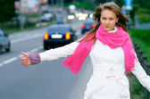Girl hitch-hike on highway — Stock Photo