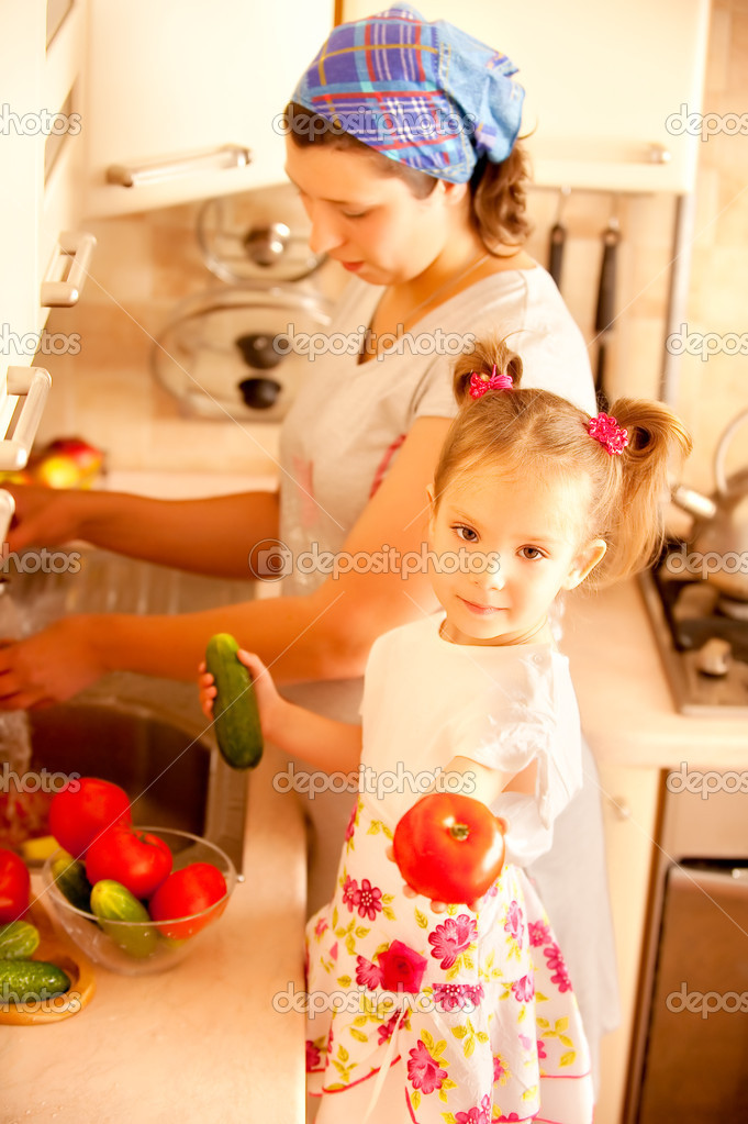 Mum and daughter wash tomatoes and cucumbers on kitchen. — Stock Photo #2588279