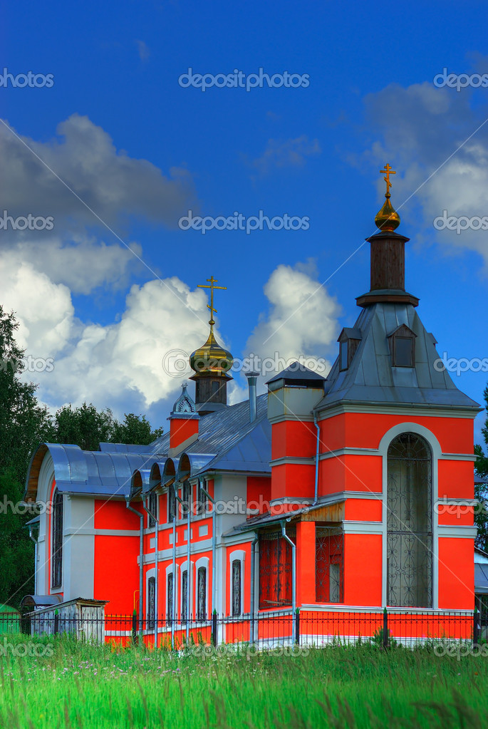 Beautiful stone church with red plaster and golden domes against the dark blue sky with clouds.  Stock Photo #2588823