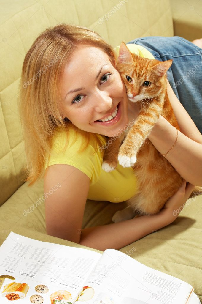 Embraces of the girl and kitten on a sofa — Stock Photo #1621896