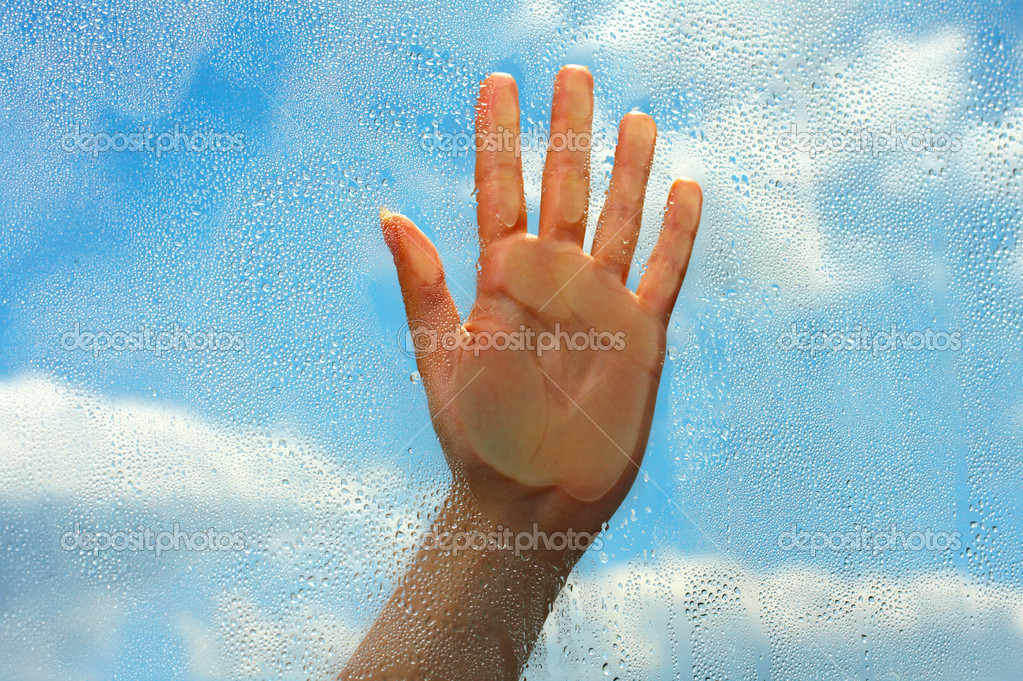 Hand on wet glass on a background of the blue sky — Stock Photo #1902100