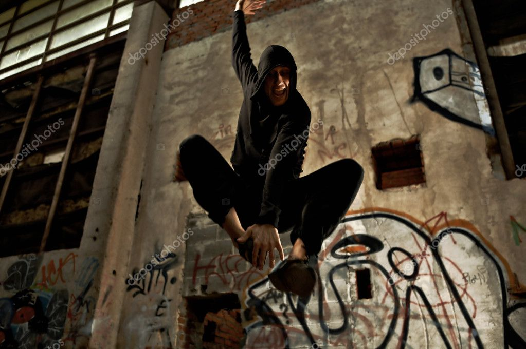 The person in black jumps inside of the thrown building with graffiti — Stock Photo #1902234