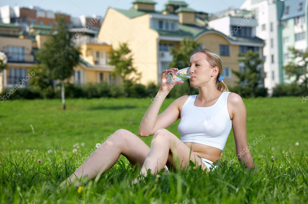 The pretty girl sits on a lawn and drinks water — Stock Photo #1902830