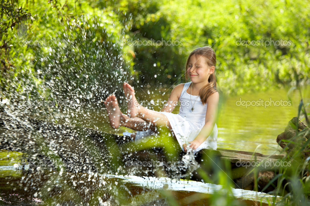 The playful girl sprays feet pond water   — Foto Stock #1902890