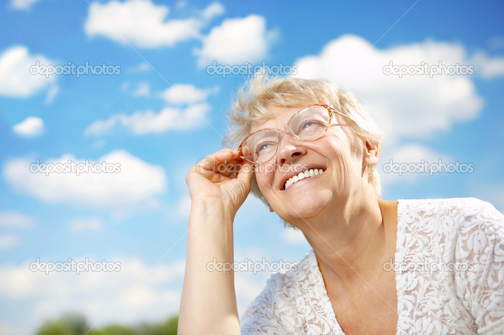 The elderly woman in glasses laughs against the sky — Stock Photo #1903634
