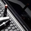 Three lipsticks on a laptop — Stock Photo