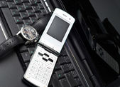 Mobile phone and watch on a laptop — Stock Photo