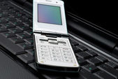 Mobile phone on a laptop — Stock Photo