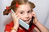 Little girl talking on two mobile phones — Stock Photo