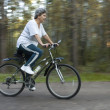 Woman on bicycle in the park — Stock Photo