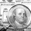 Stock Photo: Magnifier with money closeup