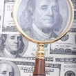 Magnifier with money — Stockfoto
