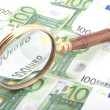 Magnifying glass with money closeup — Stock Photo