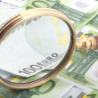 Magnifying glass with money — Stock Photo #1870640