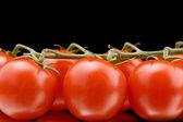 Ripe tomato on black macro — Stock Photo