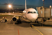 Plane parked at the airport at night — Stock Photo