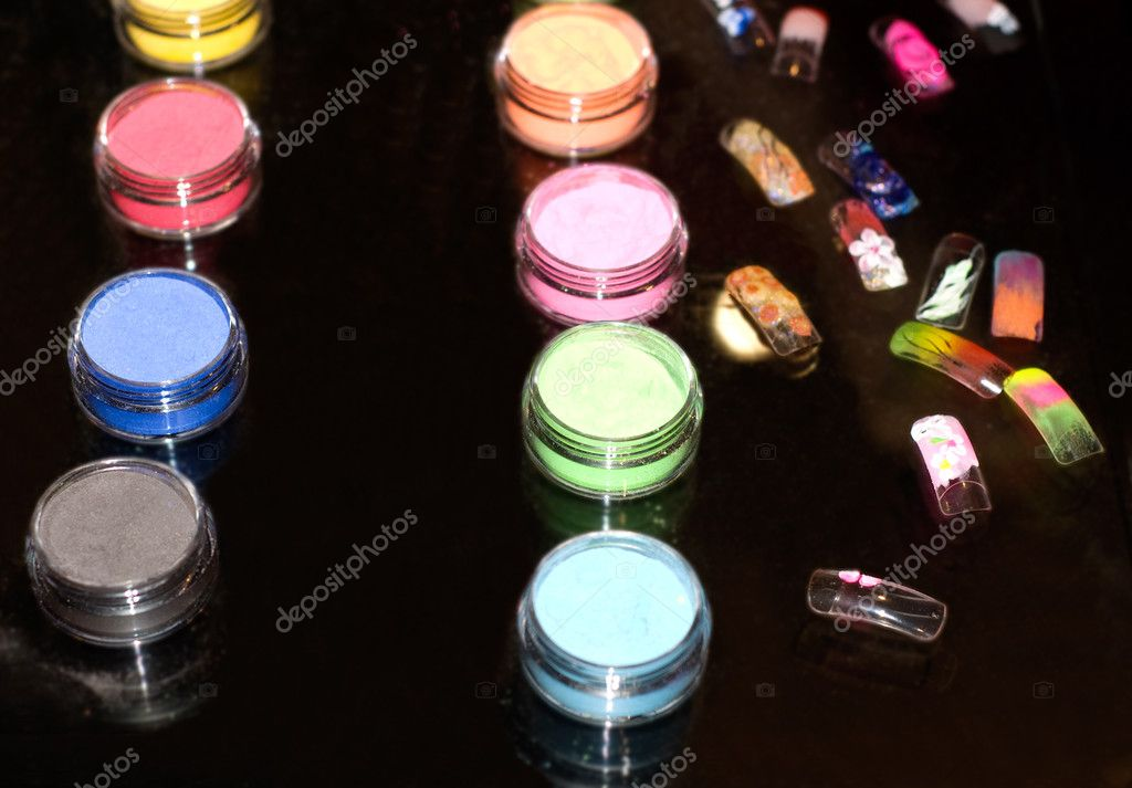 Set of powder cosmetic and fake nails on a mirror table (shallow dof) — Stock Photo #1668942