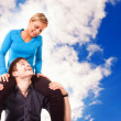 Young couple is having fun (blue sky background) — Stock Photo