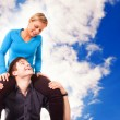 Young couple is having fun (blue sky background) - Stock Photo