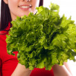 Girl is holding aleaf of salad — Stock Photo