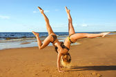 Two acrobatic girl on the beach — Stock Photo