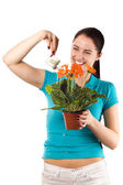 Smiling woman watering her flowers — Stock Photo