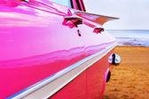Klassieke roze cadillac op strand — Stockfoto