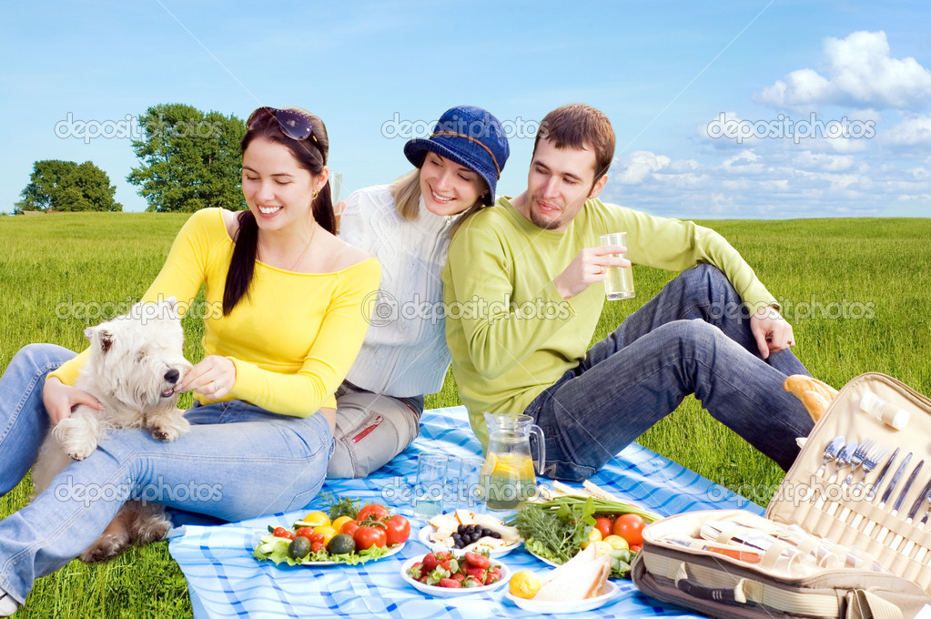 Three friends with little white dog at picnic — Stock Photo #1670398