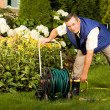 Royalty-Free Stock Photo: Man crimping hose in the garden