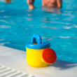 Stock Photo: Child's watering-can at the pool