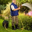 Man watering flowers in the garden — Foto de Stock