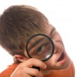 Nerd guy with magnifying glass (shallow dof) — Stock Photo