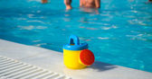 Child's watering-can at the pool — Stock Photo