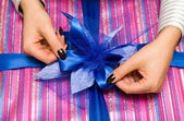 Beautiful hands wrapping giftbox — Stock Photo