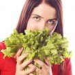 Girl is holding a leaf of salad - Stock Photo