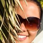 vacker ung kvinna bakom palm — Stockfoto