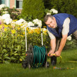 Man crimping hose in the garden - Stock Photo