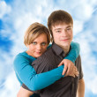Young couple hugging (blue sky background) — Stock Photo