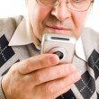 Stock Photo: Senior man typing on mobile phone