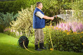 Man watering flowers in the garden — Stock Photo